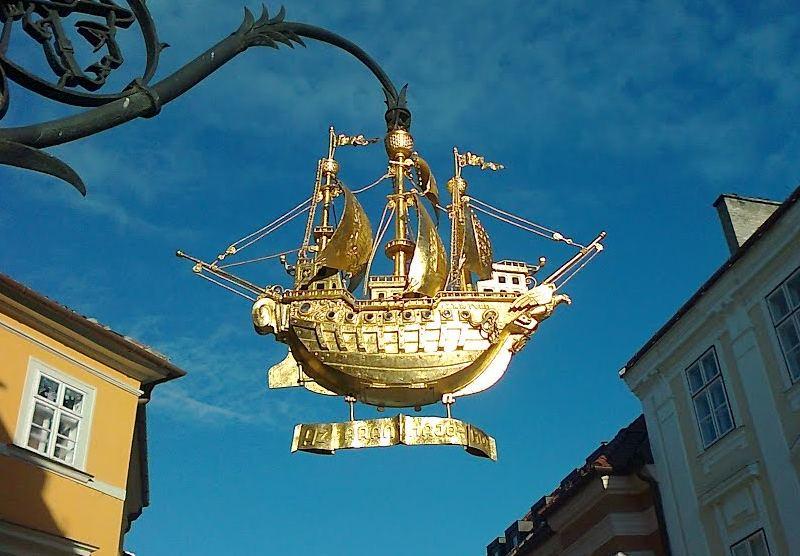 Letreiro com navio dourado pendurado